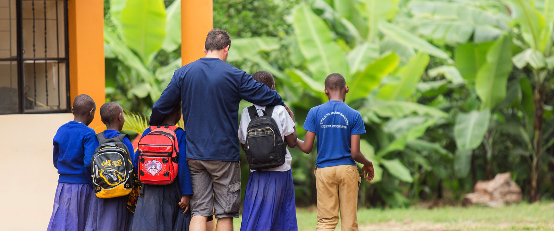 back view of a man volunteering for children in Tanzania